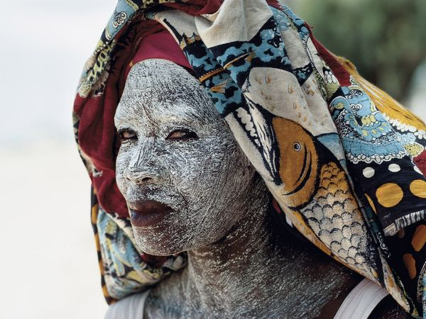 A Mozambican woman wearing face cream made from ground bark which provides protection from Mozambique's equatorial sun. This is a common practice in Mozambique. Photograph by James L. Stanfield for National Geographic
